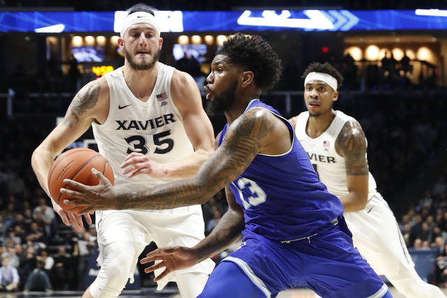Seton Hall's Myles Powell (13) passes the ball as Xavier's Zach Hankins (35) defends during the second half of an NCAA college basketball game Wednesday, Jan. 2, 2019, in Cincinnati. (AP Photo/John Minchillo)
