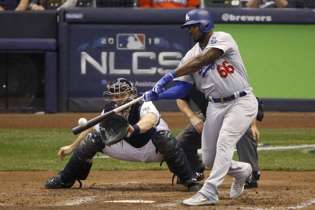 FILE - In this Oct. 20, 2018, file photo, Los Angeles Dodgers' Yasiel Puig (66) hits a three -run home run during the sixth inning of Game 7 of the National League Championship Series baseball game against the Milwaukee Brewers in Milwaukee. The Dodgers shook up their National League-championship roster Friday, Dec. 21, 2018, trading Puig, Matt Kemp and left-hander Alex Wood and cash to the Cincinnati Reds for right-hander Homer Bailey. (AP Photo/Charlie Riedel, File)