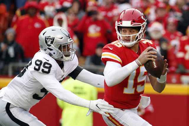 FILE - In this Sunday, Dec. 30, 2018 file photo, Kansas City Chiefs quarterback Patrick Mahomes (15) breaks a tackle-attempt by Oakland Raiders defensive end Arden Key (99) during the first half of an NFL football game in Kansas City, Mo.. For the first time in a decade, the top seed in the AFC playoffs goes to a team not led by Tom Brady or Peyton Manning. The Chiefs haven't had a true franchise QB since Len Dawson led the Chiefs to their only Super Bowl title. But after trading up to select Mahomes in the first round in 2017, then letting him learn the ropes under Alex Smith, Mahomes responded with one of the best seasons in NFL history for a first-year starter. (AP Photo/Charlie Riedel, File)