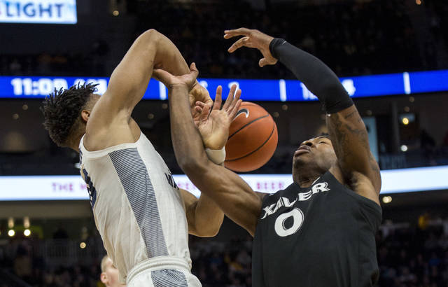 Marquette forward Ed Morrow, left, battles for the ball with Xavier forward Tyrique Jones, right, during the first half of an NCAA college basketball game Sunday, Jan. 6, 2019, in Milwaukee. (AP Photo/Darren Hauck)