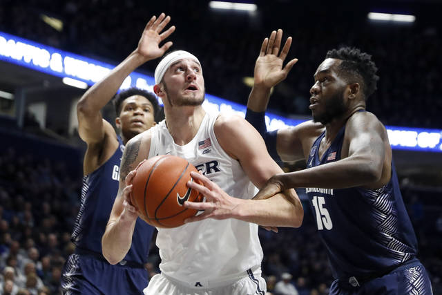 Xavier's Zach Hankins, center, eyes the basket against Georgetown's Jessie Govan (15) during the first half of an NCAA college basketball game, Wednesday, Jan. 9, 2019, in Cincinnati. (AP Photo/John Minchillo)