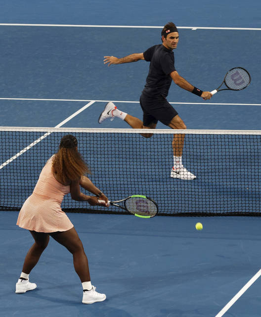 FILE - In this Jan. 1, 2019, file photo, Roger Federer of Switzerland returns the ball to Serena Williams of the United states during their mixed doubles tennis match at the Hopman Cup in Perth, Australia. It was a terrific moment for tennis, drawing tons of attention to an otherwise meaningless exhibition event and a recently dormant sport just starting its new season: Serena Williams and Roger Federer sharing a court. (AP Photo/Trevor Collens, File)