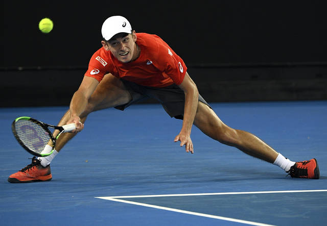 Australia's Alex de Minaur reaches for a forehand return to Switzerland's Henri Laaksonen during their second round match at the Australian Open tennis championships in Melbourne, Australia, Wednesday, Jan. 16, 2019. (AP Photo/Andy Brownbill)