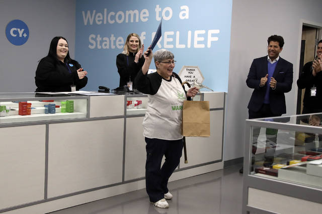 Joan Caleodis, of Martin's Ferry, Ohio, center, celebrates being one of the first patient sales of Ohio's Medical Marijuana program at Cresco Labs CY+ dispensary in Winterville, Ohio, Wednesday, Jan. 16, 2019. (AP Photo/Gene J. Puskar)