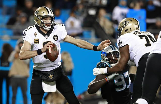 FILE - In this Dec. 17, 2018, file photo, New Orleans Saints' Drew Brees (9) scrambles away from a Carolina Panthers defender during the first half of an NFL football game in Charlotte, N.C. Offense wins championships in the new NFL. For the first time since the league expanded to 32 teams in 2002, none of the teams playing in the conference title game have a defense ranked in the top 10 in total yards. Only New England is among the top 10 in fewest points allowed. But, the Chiefs, Patriots, Saints and Rams do possess the four most prolific offenses in the league. (AP Photo/Jason E. Miczek, File)