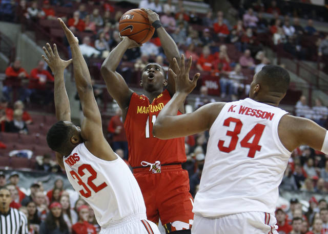 Maryland's Darryl Morsell, center, shoots over Ohio State's Keyshawn Woods, left, and Kaleb Wesson during the first half of an NCAA college basketball game Friday, Jan. 18, 2019, in Columbus, Ohio. (AP Photo/Jay LaPrete)