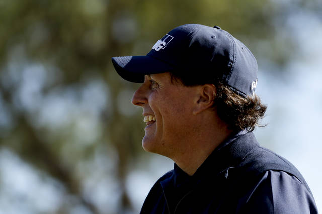 Phil Mickelson smiles after his tee shot on the fourth hole during the third round of the Desert Classic golf tournament on the Stadium Course at PGA West on Saturday, Jan. 19, 2019, in La Quinta, Calif. (AP Photo/Chris Carlson)