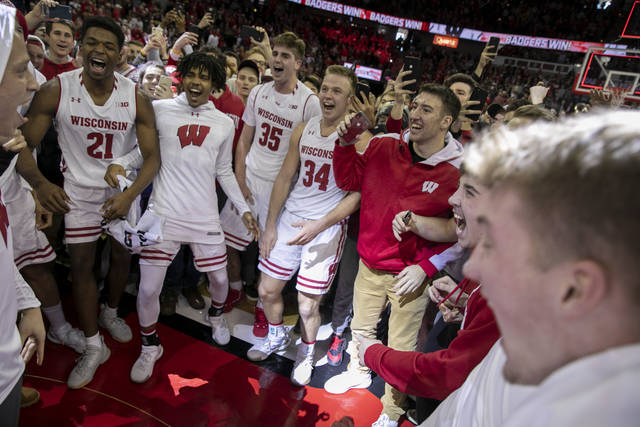 Wisconsin players and fans celebrate Wisconsin's 64-54 upset victory over Michigan in an NCAA college basketball game Saturday, Jan. 19, 2019, in Madison, Wis. (AP Photo/Andy Manis)