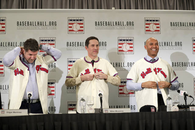 Baseball Hall of Fame inductees Edgar Martinez, left, Mike Mussina, center, and Mariano Rivera, right, put on jerseys during news conference Wednesday, Jan. 23, 2019, in New York. (AP Photo/Frank Franklin II)