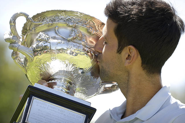 Serbia's Novak Djokovic poses with his trophy, the Norman Brookes Challenge Cup, at Melbourne's Royal Botanic Gardens following his win over Rafael Nadal of Spain in the men's singles final at the Australian Open tennis championships in Melbourne, Australia, Monday, Jan. 28, 2019. (AP Photo/Mark Schiefelbein)