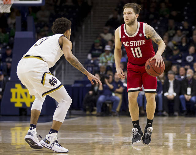 File- This Jan. 19, 2019, file photo shows North Carolina State's Braxton Beverly (10) getting  pressure from Notre Dame's Prentiss Hubb (3) during the second half of an NCAA college basketball game in South Bend, Ind. Beverly hit the last-second 3-pointer to beat Clemson for No. 23 N.C. State, which hosts No. 3 Virginia and No. 12 Virginia Tech this week. (AP Photo/Robert Franklin, File)