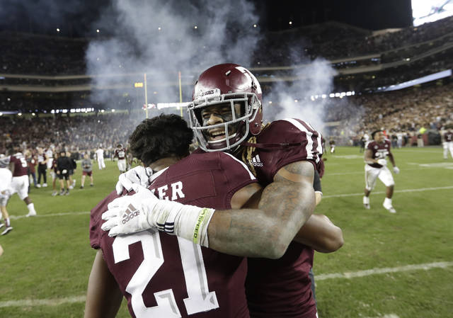 FILE - In this Nov. 24, 2018, file photo, Texas A&M wide receiver Kendrick Rogers, right, celebrates with Charles Oliver (21) after their 74-72 win in seven overtimes against LSU in an NCAA college football game in College Station, Texas. Marathon overtime games in college football, like the one Texas A&M and LSU played last season, are rare. The NCAA would like to make them extinct by tweaking its overtime format. (AP Photo/David J. Phillip, File)