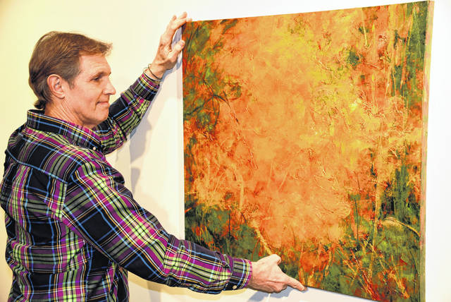 "Harcum Gallery curator Hal Shunk hangs an acrylic painting by Linda Stanforth titled ""Haskins Arboretum."""