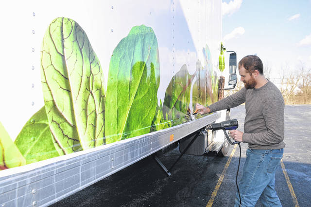 P.J. Addison of Graphics to Go in Wilmington begins the process of decorating the BrightFarms truck.