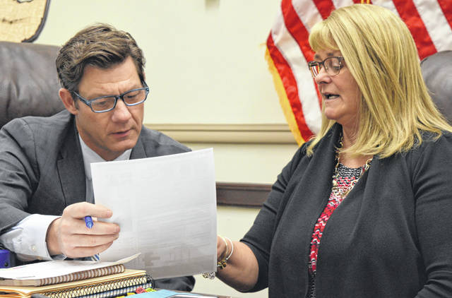 From left, Clinton County Commissioner Kerry R. Steed and Clinton County Commissioners President Brenda K. Woods find a paper useful as they conduct county business this week.