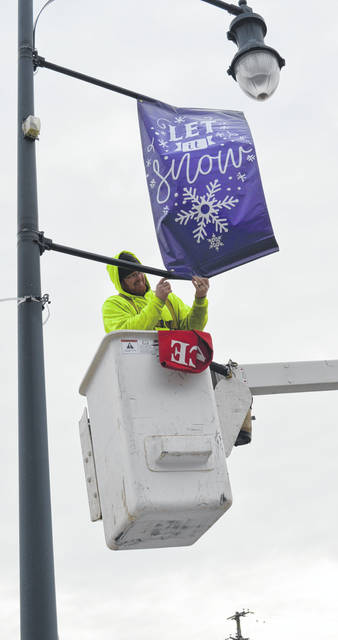 "In an effort to add a little splash of color to the downtown during winter's gray days, a City of Wilmington crew was hanging seasonal banners Monday to the street light poles. The City paid for the banners using hotel lodging tax funds. In the photo, Seth Horsley of the Wilmington Maintenance & Repair/Streets Department installs a banner on the courthouse block of Sugartree Street. The message ""Let it Snow"" holds some irony for Horsley — he's one of the City employees who salt and clear the streets when winter weather strikes."