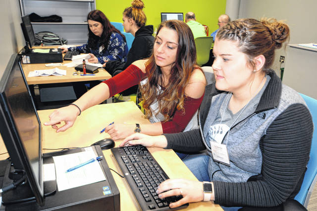 Seniors Tara Karnes, right, and Tabby Williamson, pictured in March, look over a tax return before approving it for filing. Tara served as the student site coordinator and graduated in May with an accounting job in her pocket.