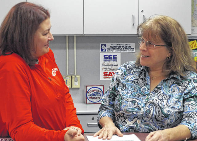 Newly appointed Clinton-Massie school board member Kathleen Norman, right, converses Monday with Clinton-Massie Treasurer Carrie C. H. Bir, left, who's in her first month on the job.