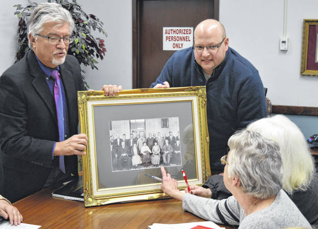 "Clinton County Common Pleas Judge John W. ""Tim"" Rudduck, left, shows other members of the 100th Anniversary Committee a re-conditioned photo that's believed to show the first women jurors in the history of the county. Clockwise from Rudduck are Jeff Walls, Jennifer Hollon and Kay Fisher."