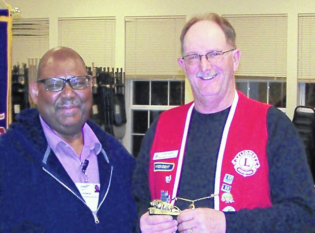 Lions Club President John Hibbs, right, presents a Lion statuette to Vermon Dillon.