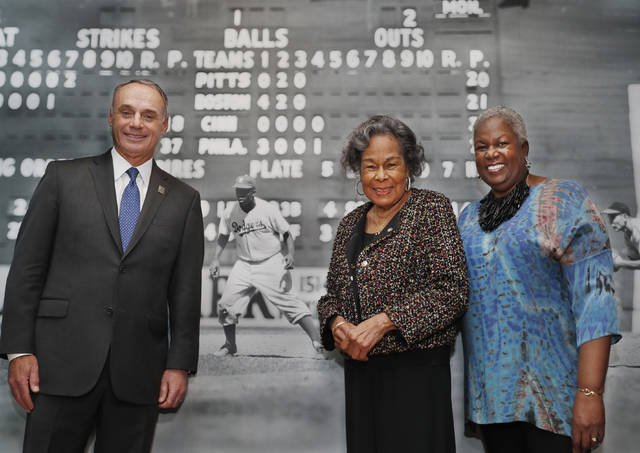 "Major League Baseball Commissioner Rob Manfred, left, Rachel Robinson, center, widow of the late Jackie Robinson, and Sharon Robinson, the couple's daughter, pose in front of a mural-sized photograph of Jackie Robinson in uniform displayed at the Museum of the City of New York, Thursday, Jan. 31, 2019, in New York. The photo is part of ""In the Dugout with Jackie Robinson,"" an exhibition celebrating Robinson's 100th birthday, mounted in collaboration with The Jackie Robinson Foundation. The exhibit features 30 photographs originally shot for Look Magazine (most never published) and rare Robinson family home movies plus memorabilia related to Robinson's career. (AP Photo/Kathy Willens)"