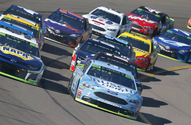 FILE- In this Nov. 11, 2018, file photo Kevin Harvick (4) leads the field for the green flag start during a NASCAR Cup Series auto race in Avondale, Ariz. NASCAR has radically revamped its racing packing in an aggressive push to improve its on-track product. (AP Photo/Rick Scuteri, File)