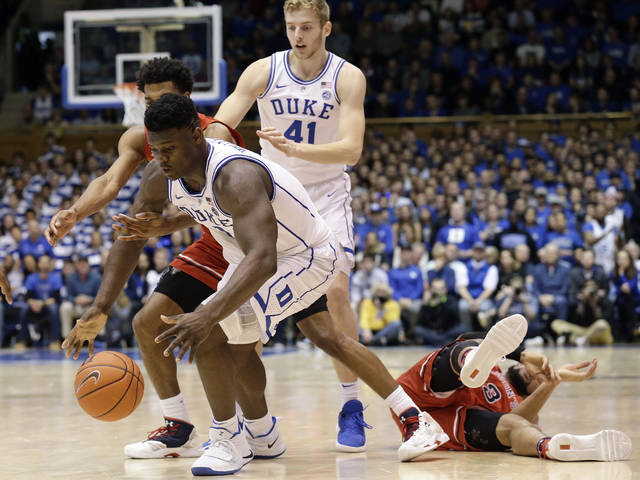 Duke's Zion Williamson reaches for the ball with St. John's Justin Simon while St. John's Marvin Clark II falls and Duke's Jack White looks on during the second half of an NCAA college basketball game in Durham, N.C., Saturday, Feb. 2, 2019. (AP Photo/Gerry Broome)