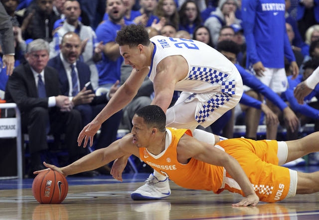 Kentucky's Reid Travis, top, and Tennessee's Grant Williams chase down a loose ball during the first half of an NCAA college basketball game in Lexington, Ky., Saturday, Feb. 16, 2019. (AP Photo/James Crisp)