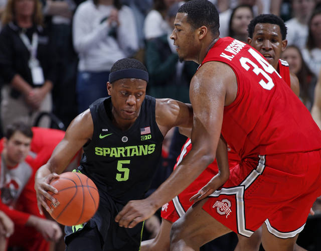 Michigan State's Cassius Winston, left, drives against Ohio State's Kaleb Wesson during the first half of an NCAA college basketball game, Sunday, Feb. 17, 2019, in East Lansing, Mich. (AP Photo/Al Goldis)