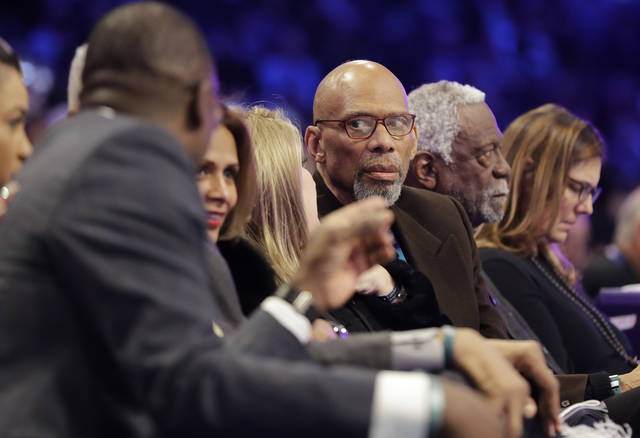 Former NBA player Kareem Abdul-Jabbar, center, speaks with Dominque Wilkins, left, as former player Bill Russell is seen at right, during the NBA All-Star skills session basketball contest, Saturday, Feb. 16, 2019, in Charlotte, N.C. (AP Photo/Chuck Burton)
