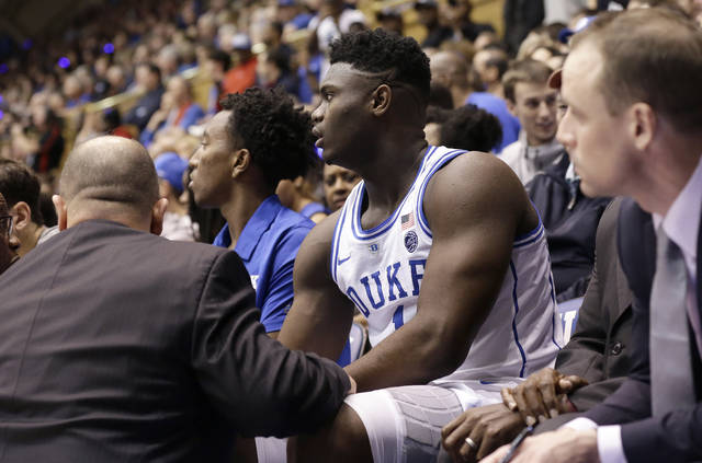 c35e2645582 Duke s Zion Williamson (1) is attended to on the bench following an injury  during the first half of an NCAA college basketball game against North  Carolina ...