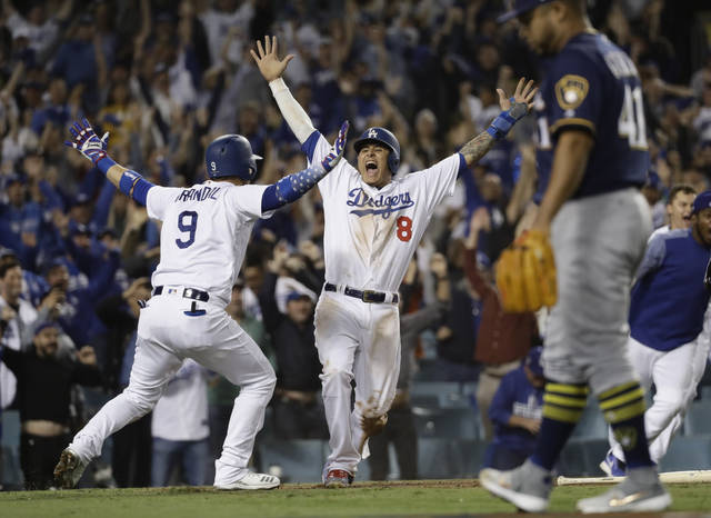 FILE - In this Oct. 16, 2018, file photo, Los Angeles Dodgers' Manny Machado (8) reacts after scoring on a Cody Bellinger walk-off hit during the 13th inning of Game 4 of the National League Championship Series baseball game against the Milwaukee Brewers, in Los Angeles. A person familiar with the negotiations tells The Associated Press that infielder Manny Machado has agreed to a $300 million, 10-year deal with the rebuilding San Diego Padres, the biggest contract ever for a free agent. The person spoke to the AP on condition of anonymity Tuesday, Feb. 19, 2019,  because the agreement was subject to a successful physical and had not been announced. (AP Photo/Matt Slocum, File)