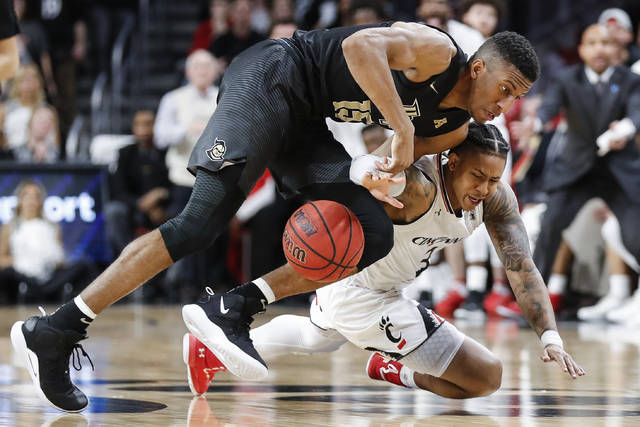 Cincinnati guard Justin Jenifer (3) and Central Florida guard Aubrey Dawkins (15) scramble for a loose ball during the first half of an NCAA college basketball game Thursday, Feb. 21, 2019, in Cincinnati. (AP Photo/John Minchillo)