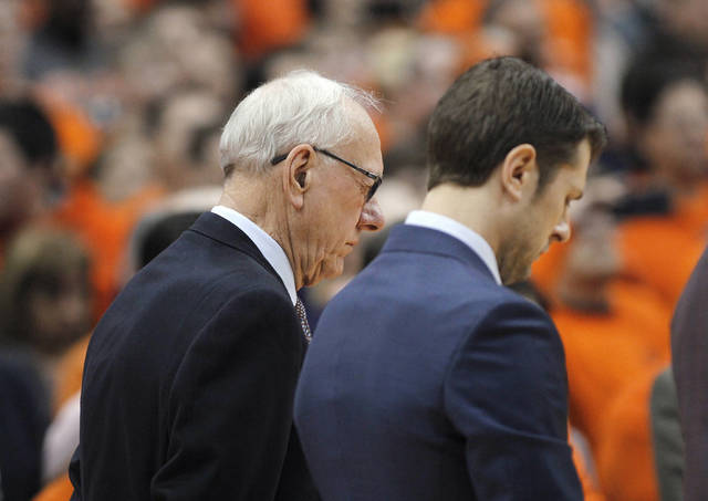 Syracuse coach Jim Boeheim, left, bows his head during a moment of silence for the man killed in a fatal crash involving coach Boeheim, before the team's NCAA college basketball game against Duke in Syracuse, N.Y., Saturday, Feb. 23, 2019. Duke won 75-65. (AP Photo/Nick Lisi)
