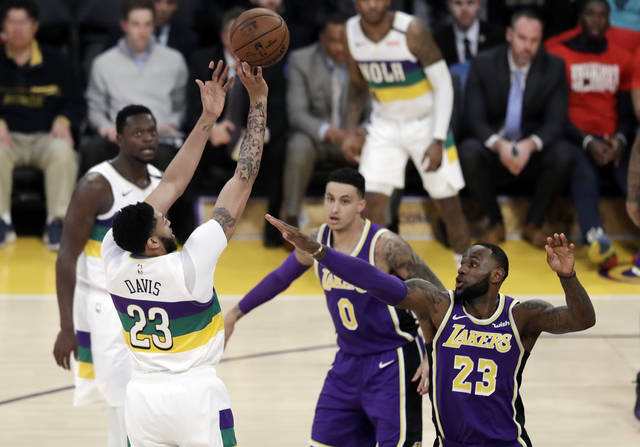 New Orleans Pelicans' Anthony Davis, left, shoots over Los Angeles Lakers' LeBron James (23) during the first half of an NBA basketball game Wednesday, Feb. 27, 2019, in Los Angeles. (AP Photo/Marcio Jose Sanchez)