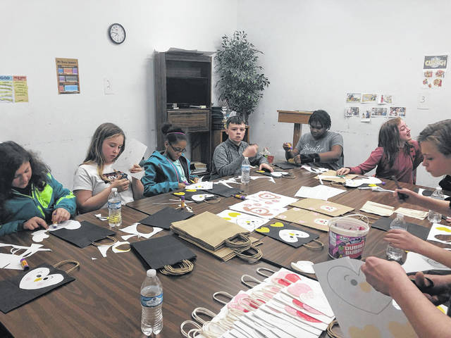The Holy Hurricane Club at Wilmington Middle School gives a hand to Brylin Ruddle, fourth from left, in constructing the nearly 500 Valentine's bags to make sure no elementary student goes without a bag.