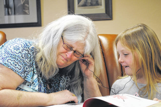 Tara DiMario, left, listens to recordings of her deceased daughter, Erin Payne, with her granddaughter and Erin's daughter, Madison. The MP3 with the recordings was given to them from StoryChain out of Dayton.