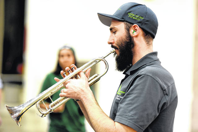 Stephen Wadsack, director of athletic bands and instructor of music, plays trumpet while directing the Quaker Thunder Pep Band at a 2019 season basketball game.