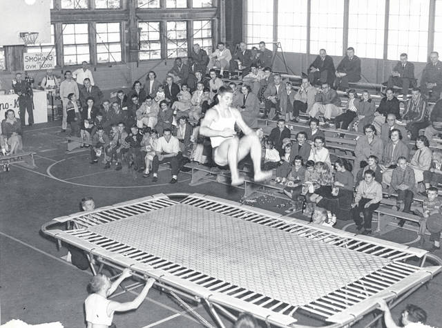 "This photo was taken in one of the original hangars of the Clinton County Air Force Base. The gymnastic troupe was from the University of Maryland and was invited to perform at a ""Gymkana"" by Lt. Milligan, himself a gymnast. He was later one of the victims of the air disaster. The group returned in 1958 and the public was invited to the performances. WNJ reader Joyce Hater Wells, who worked on the base, is seated on the left, about three rows from the top, next to her younger brother, Ed Hater. In the top row on the right are Lt. Kay, Information Services Officer, and Col. Bentley, the Base Commander. Does anyone remember this or recognize anyone in the photo? Let us know at info@wnewsj.com."