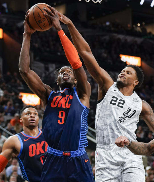 Oklahoma City Thunder's Jerami Grant (9) attempts to shoot against San Antonio Spurs' Rudy Gay (22) as Thunder guard Russell Westbrook looks on during the first half of an NBA basketball game, Saturday, March 2, 2019, in San Antonio. (AP Photo/Darren Abate)