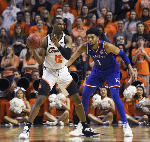 Oklahoma State forward Cameron McGriff (12) looks for an open teammate while under pressure from Kansas forward Dedric Lawson (1) during an NCAA college basketball game in Stillwater, Okla., Saturday, March 3, 2019. Lawson led Kansas scoring with 20 points in the 72-67 win over Oklahoma State. (AP Photo/Brody Schmidt)