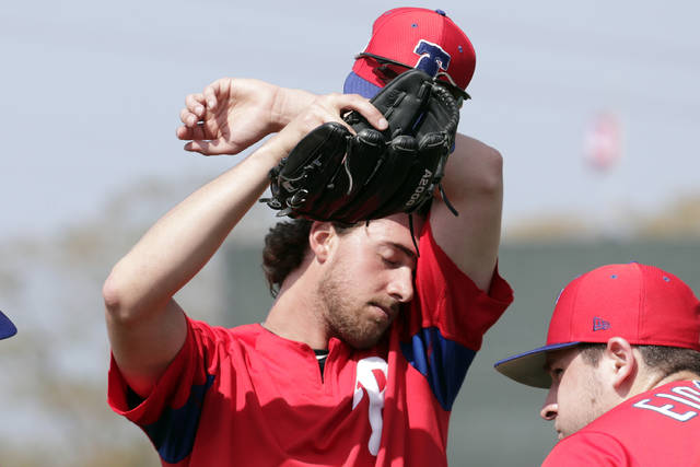 FILE - In this Feb. 19, 2019, file photo, Philadelphia Phillies starting pitcher Aaron Nola wipes his face at the Phillies spring training baseball facility, in Clearwater, Fla. It may look like a few weeks of relaxed fun in the sun, but make no mistake: Spring training can be a grind. Pitchers need to build their arms up slowly, and position players face their own challenges. At this time of year, Florida and Arizona are obviously better for baseball than many other American climates, but the warm, sunny weather does have a few drawbacks. (AP Photo/Lynne Sladky, File)