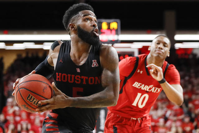 Houston's Corey Davis Jr., left, drives past Cincinnati's Rashawn Fredericks (10) in the second half of an NCAA college basketball game, Sunday, March 10, 2019, in Cincinnati. (AP Photo/John Minchillo)
