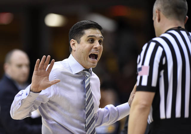 UNC-Greensboro head coach Wes Miller, left, argues a call with a referee in the first half of an NCAA college basketball game against Wofford for the Southern Conference tournament championship, Monday, March 1, 2019, in Asheville, N.C. (AP Photo/Kathy Kmonicek)