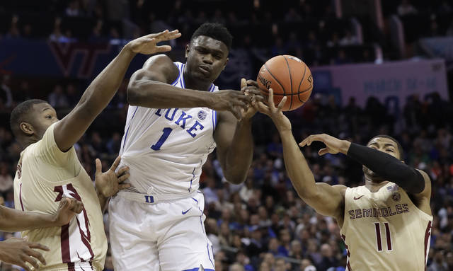 Duke's Zion Williamson, center, loses the ball as he is trapped by Florida State's David Nichols, right, and Raiquan Gray, left, during the first half of the NCAA college basketball championship game of the Atlantic Coast Conference tournament in Charlotte, N.C., Saturday, March 16, 2019. (AP Photo/Chuck Burton)