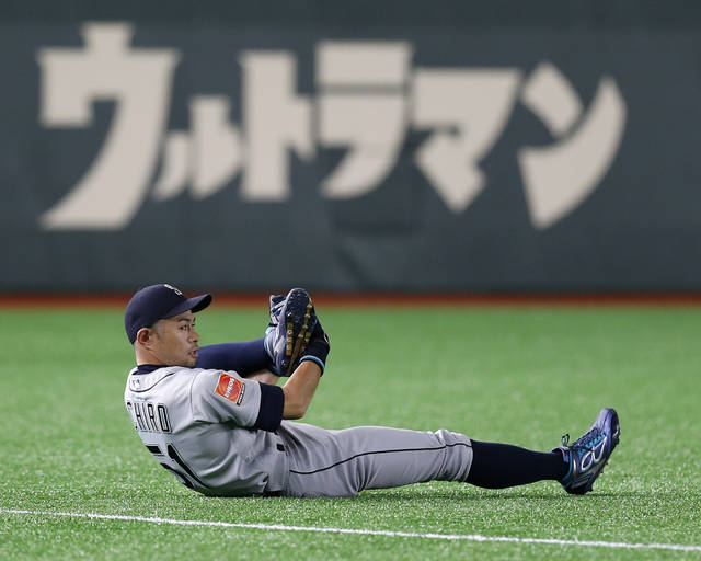 "Seattle Mariners right fielder Ichiro Suzuki stretches on the field prior to Game 2 of the Major League baseball opening series between the Mariners and the Oakland Athletics at Tokyo Dome in Tokyo, Thursday, March 21, 2019. Ichiro is in the starting lineup for the Mariners in what might be his last game in the majors. Japanese in the background reads: ""Ultraman."" (AP Photo/Toru Takahashi)"