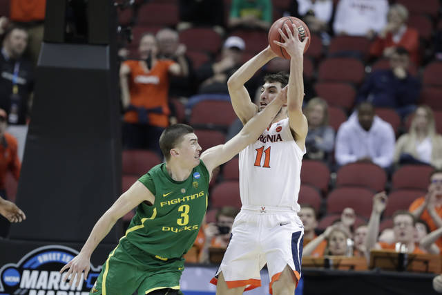 Virginia's Ty Jerome (11) is fouled by Oregon's Payton Pritchard (3) during the second half of a men's NCAA Tournament college basketball South Regional semifinal game, Friday, March 29, 2019, in Louisville, Ky. Virginia won 53-49. (AP Photo/Michael Conroy)