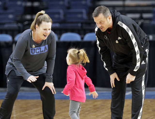UCLA head coach Cori Close, left, reacts as the daughter of Louisville head coach Jeff Walz, center, runs on the court to greet her father, right, during  practice at the NCAA women's college basketball tournament, Thursday, March 28, 2019, in Albany, N.Y. UCLA faces UConn, and Louisville faces Oregon State in NCAA regional semifinal games on Friday. (AP Photo/Kathy Willens)