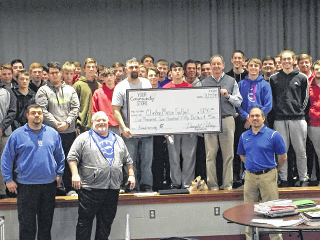 Clinton-Massie football coaches Jeskee Zantene (front left), Dan McSurley (front left) and Scott Rolf (front right) and the football program received a check from We Help Others, the parent company of Your Community Store. Holding the check are Darrell Petry, left, of We Help Others and Al Bell, right, of the Caesar Creek Flea Market.