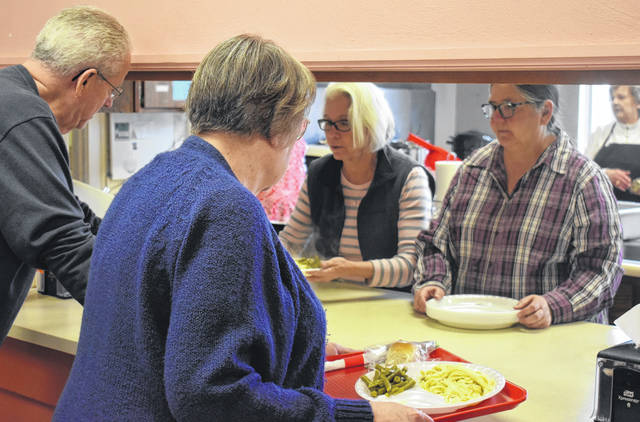 From left, Herb and Sharyn Johnson get their lunch of chicken and noodles and more from Lorry Swindler and Tari Mabry at the Wilmington United Methodist Church's Lenten Lunch on Wednesday. The event continues next Wednesday from 11 a.m. to 1 p.m; cost is $7.